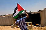 A Palestinian protester holds the Palestinian flag in front of a gate in Israel's controversial separation barrier built on Palestinian land in the village of Ni'lin near Ramallah on 16/07/2010.