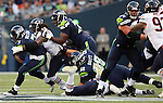 Seattle Seahawks' quarterback Russell Wilson (5) is sacked by Chicago Bears' defensive end Willie Young (97) in a pre-season game at CenturyLink Field in Seattle, Washington on August 12, 2014.  Attempting to block Young is tackle Russell Okung (76) and tackle Justin Britt (68). Seattle beat Chicago 34-6. Wilson completed 15 of 20 passes for 202 yards passed for two touchdowns and ran for another in the win. © 2014.  Jim Bryant Photo. ALL RIGHTS RESERVED.