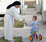 Dominican Sister St. Elene greets 2-year old Yusef Firas in Ankawa, Iraq. The nun, and the boy's family, were all displaced from Mosul by ISIS in 2014. The sister is a member of the Dominican Sisters of St. Catherine of Siena.