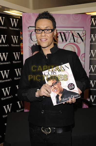 "GOK WAN.Singing copies of his new book ""How To Dress"" at Waterstone's in Bluewater, Kent, England, October 10th 2008..half length glasses black rimmed jacket trousers belt .CAP/FIN.©Steve Finn/Capital Pictures"