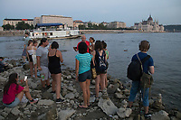 Large group of people stand on a reef under a bridge emerging from the water because of the low water level of River Danube in central Budapest, Hungary on Aug. 22, 2018. ATTILA VOLGYI