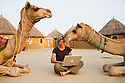 Woman with laptop sitting between curious camels in desert camp; Rajasthan, India --- Model Released