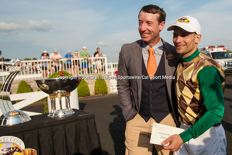 oAUG 16, 2014: Hardest Core jockey Eriluis Vaz (right) walks with the connections after winning the Arlington Million at Arlington International Race Track in Arlington Heights, IL. Jon Durr/ESW/Cal Sport Media