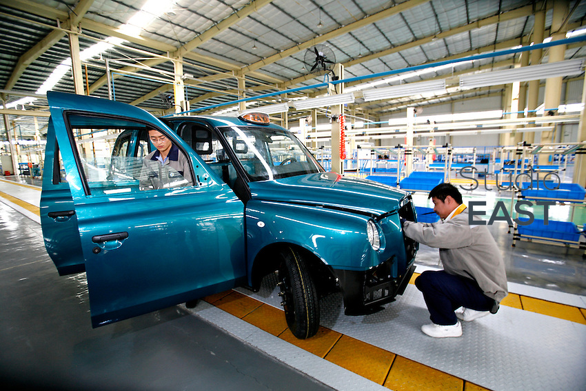 Two workers work on an hand-built and hand-welded Taxi cab in SMA factory plant, in Fengjing, outside Shanghai, China, on October 24, 2008.  London Taxi International, the producer of London Taxi's famed black cabs, turned to China to drive overseas expansion. More than 8,000 London Taxis will be produced from the Chinese factory, more than double the annual output of the firm's historical factory plant in Conventry, England. Most of these cars will go to places like Singapore, Dubai, Moscow, that covet the image associated with the London Taxis' tradition of good service and durability. London Taxi International will continue to build 90 percent of the Taxi cabs used in Britain at Coventry. Photo by Lucas Schifres/Pictobank