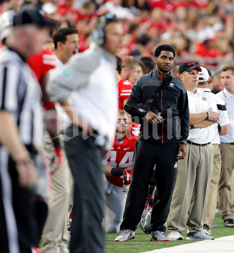 Braxton Miller watches as Ohio State Buckeyes head coach Urban Meyer yells at Ohio State Buckeyes quarterback J.T. Barrett (16) during the second quarter of Saturday's NCAA Division I football game at Ohio Stadium in Columbus on September 27, 2014. (Columbus Dispatch photo by Jonathan Quilter)