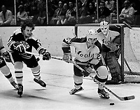 California Golden Seals Ted McAneeley with Boston Bruins Andre Savard..(1974