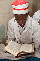 Zanzibar, Tanzania.  Young Boy in Madrassa (Koranic School), Reading the Koran.