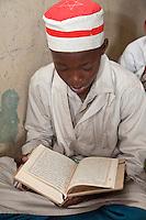 Zanzibar, Tanzania.  Young Boy in Madrassa (Koranic School), Reading the Koran.