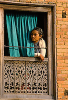 Young woman at carved window in Patan, Nepal