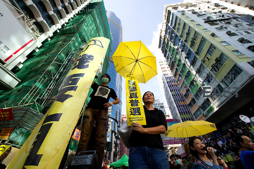 HONG KONG, CHINA - NOVEMBER 25: Pro-democracy protesters hold umbrellas, symbols of the Umbrella movement, and a banner that reads 'I want universal suffrage', in the Mongkok area in the presence of bailiffs on November 25, 2014 in Hong Kong, Hong Kong Special Administrative Region, China. The Mong Kok protest site is scheduled for clearance by baliffs this week after Hong Kong's high court authorized police to arrest protesters who obstruct bailiffs on the three interim restraining orders. (Photo by Lucas Schifres/Getty Images)