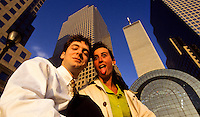Young couple making faces below skyscrapers and  World Trade Center, New York City, USA