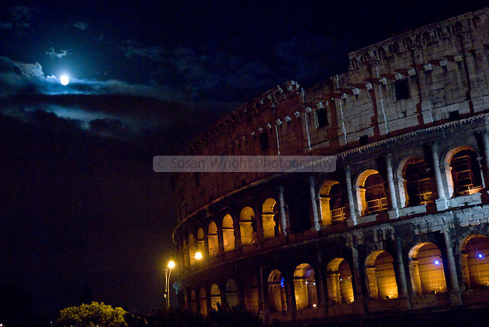 The Colosseum illuminated at night beneath a full moon, Rome Italy