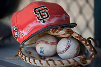 A San Francisco Giants Orange hat and glove in the dugout during an Extended Spring Training game against the Oakland Athletics at the Lew Wolff Training Complex on May 29, 2018 in Mesa, Arizona. (Zachary Lucy/Four Seam Images)