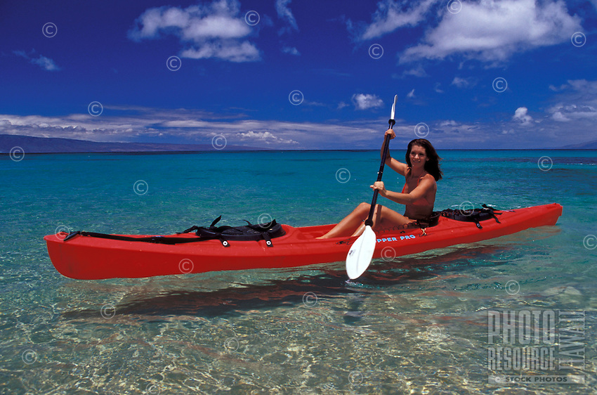 Girl paddles red kayak through the clear water of Napili Bay, Maui.