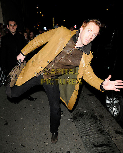 "DAMIEN LEWIS .Departing an evening performance of ""The Misanthorpe"", Comedy Theatre, London, England..February 22nd, 2010.full length jeans denim black brown yellow leather jacket leg up bending leaning funny damian .CAP/CAN.©Can Nguyen/Capital Pictures."