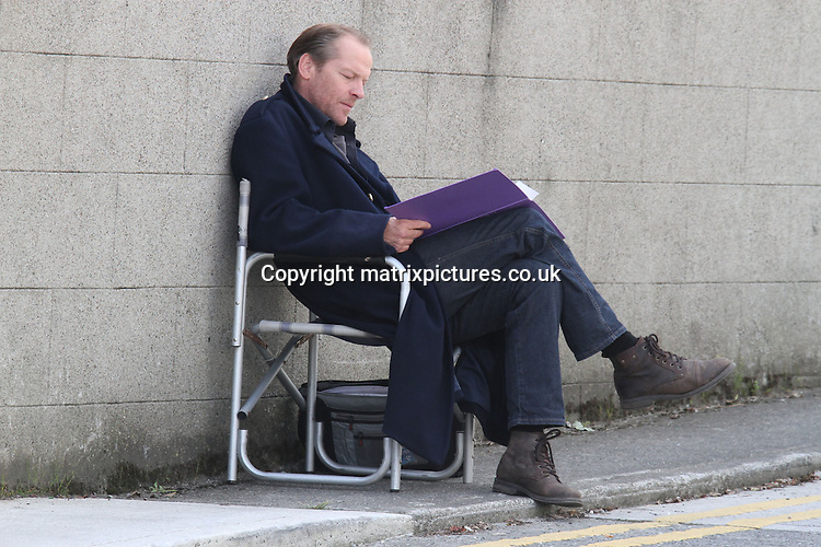 EXCLUSIVE ALL ROUND PICTURE: MATRIXPICTURES.CO.UK<br /> PLEASE CREDIT ALL USES<br /> <br /> WORLD RIGHTS EXCEPT IRELAND<br /> <br /> Scottish actor Iain Glen is pictured in costume while filming on location for the 6th &quot;Jack Taylor&quot; TV-movie in Bray, Ireland.<br /> <br /> Under the direction of Stuart Orme, todays scenes saw a car speeding around the corner next to Bray Garda Station, with a young girl running and Iain - as title character Jack Taylor - chasing her. <br /> <br /> In between takes an umbrella was used to keep the sun from Iain's face as read his lines and listened to a dictaphone.<br /> <br /> JUNE 19th 2013<br /> <br /> REF: MDE 134188