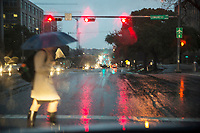 A State of Texas office worker holding a umbrella during a rain storm crosses Congress Avenue in downtown Austin, Texas.