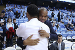 28 December 2016: UNC assistant coach Hubert Davis (behind) embraces for college teammate at UNC and Monmouth head coach King Rice. The University of North Carolina Tar Heels hosted the Monmouth University Hawks at the Dean E. Smith Center in Chapel Hill, North Carolina in a 2016-17 NCAA Division I Men's Basketball game. UNC won the game 102-74.
