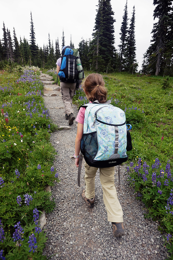 Female child and mother backpacking on trail, Spray Park, Mount Rainier National Park, Washington State, USA