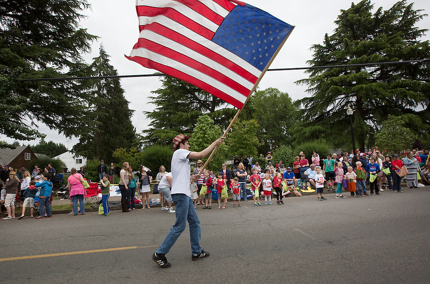 Josh Surdu waves a giant flag as he takes part in the Fourth of July Parade through Ridgefield Monday July 4, 2016. (Photo by Natalie Behring/ for the The Columbian)