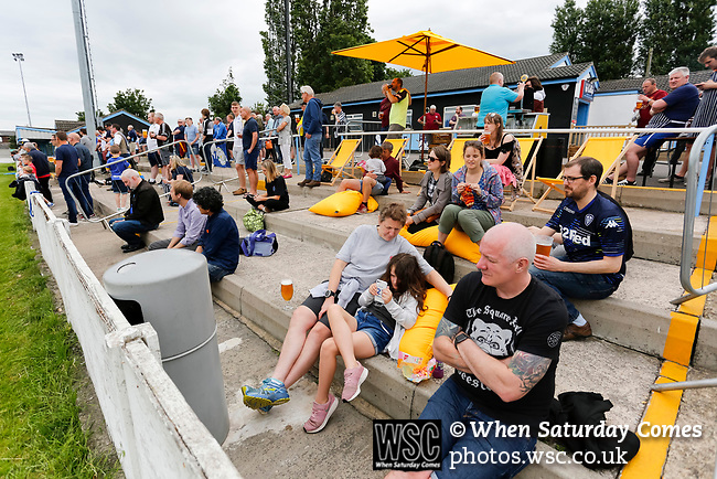 Not everyone in the outdoor bar area is fully focused on the game. Yorkshire v Parishes of Jersey, CONIFA Heritage Cup, Ingfield Stadium, Ossett. Yorkshire's first competitive game. The Yorkshire International Football Association was formed in 2017 and accepted by CONIFA in 2018. Their first competative fixture saw them host Parishes of Jersey in the Heritage Cup at Ingfield stadium in Ossett. Yorkshire won 1-0 with a 93 minute goal in front of 521 people. Photo by Paul Thompson