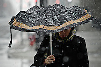 Snow falls as a woman make their way in Jersey City during the season's first snow storm on December 10, 2013 in New York City Photo by Kena Betancur / VIEWpress.