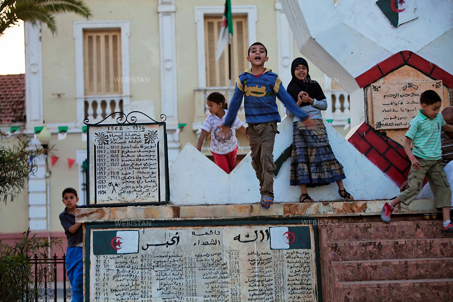 Algerie. Village El Malah_Rio Salado. 14 Avril 2011.Sur la place de la mairie, des enfants s'amusent devant un monument dedie aux martyrs (&laquo; moujahidines &raquo;) morts durant la guerre d'Algerie (1954 - 1962).<br />