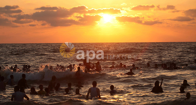 Palestinians enjoy a day at the beach of the Mediterranean Sea on the coast of Gaza City, on June 12, 2015. Photo by Ashraf Amra