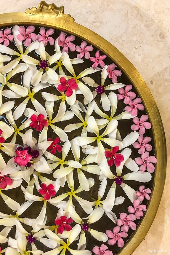 A large shallow bowl of water artfully covered in assorted floating flower blossoms at a hotel in Thiruvananthapuram, Kerala, India,  June 7, 2017.   (Cellphone Photo by Cheryl Senter)