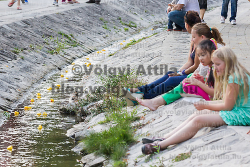 Children watch a thousand rubber ducks float on a creek during a charity race of the Rotary Club in Szentendre (about 20 km North of the capital city Budapest), Hungary on August 31, 2013. ATTILA VOLGYI