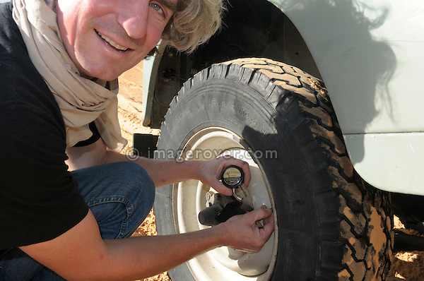 Africa, Tunisia, nr. Tembaine. Desert traveller Stephan reducing the tyre pressure on his historic 1975 Land Rover Series 3 Station Wagon before traversing through a sandfield close to Tembaine on the eastern edge of the Grand Erg Oriental. --- No releases available, but releases may not be needed for certain uses. Automotive trademarks are the property of the trademark holder, authorization may be needed for some uses.  --- Info: Image belongs to a series of photographs taken on a journey to southern Tunisia in North Africa in October 2010. The trip was undertaken by 10 people driving 5 historic Series Land Rover vehicles from the 1960's and 1970's. Most of the journey's time was spent in the Sahara desert, especially in the area around Douz, Tembaine, Ksar Ghilane on the eastern edge of the Grand Erg Oriental.