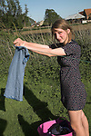 Model released image of teenage girl hanging up clothes on a washing line in Suffolk, England, UK