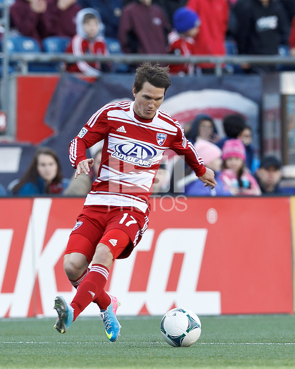 FC Dallas defender Zach Loyd (17) controls the ball at midfield. .  In a Major League Soccer (MLS) match, FC Dallas (red) defeated the New England Revolution (blue), 1-0, at Gillette Stadium on March 30, 2013.