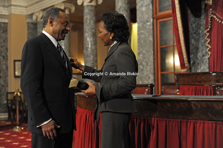 Senator Roland Burris is assisted by his wife Berlean Burris in putting on his members' pin before a swearing in ceremony in the old Senate chamber of the U.S. Senate in Washington, DC on January 15, 2008.
