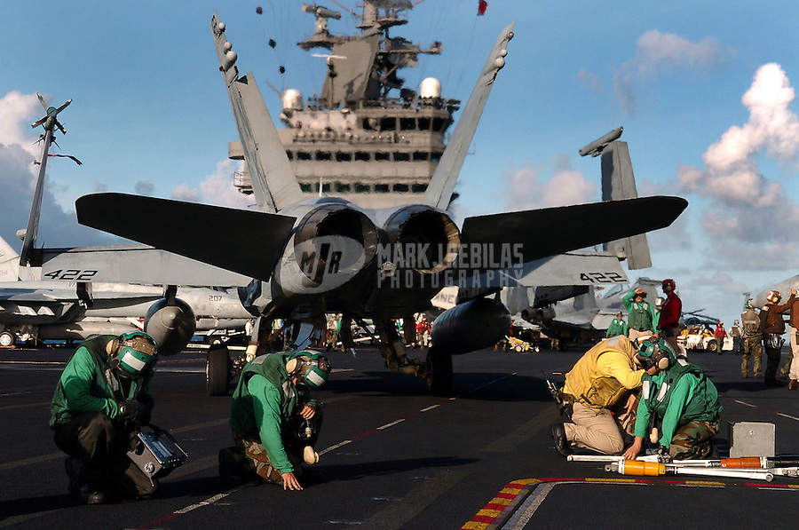 """040718-N-6213R-003 Pacific Ocean (July 18, 2004)-  Flight deck personnel crouch down to avoid the searing exhaust of an F/A-18C Hornet from the """"Fist of the Fleet"""" of Strike Fighter Squadron Two Five (VFA-25) as it turns on the flight deck aboard USS John C. Stennis (CVN 74) prior to a scheduled mission. The flight deck of an aircraft carrier is one of the most dangerous places in the world, flight deck personnel must constantly pay attention to what is going on around them. The ship and Carrier Air Wing Fourteen (CVW-14) are taking part in Rim of the Pacific (RIMPAC) 2004, during her scheduled deployment supporting the Navy's new Fleet Response Plan (FRP) Summer Pulse 2004. RIMPAC is the largest international maritime exercise in the waters around the Hawaiian Islands. This year's exercise includes seven participating nations; Australia, Canada, Chile, Japan, South Korea, United Kingdom and United States. RIMPAC is intended to enhance the tactical proficiency of participating units in a wide array of combined operations at sea, while enhancing stability in the Pacific Rim region. Photo by Mark J. Rebilas"""