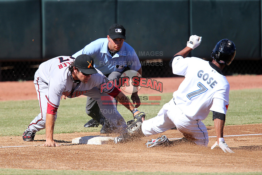 Salt River Rafters third baseman Ryan Wheeler #27 attempts to tag Anthony Gose #7 sliding in as umpire Adam Hamari looks on during an Arizona Fall League game against the Phoenix Desert Dogs at Phoenix Municipal Stadium on November 1, 2011 in Phoenix, Arizona.  Salt River defeated Phoenix 10-7.  (Mike Janes/Four Seam Images)