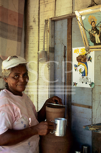Rio Negro, Brazil. Woman getting water from a big jar; Christ picture on the wall.