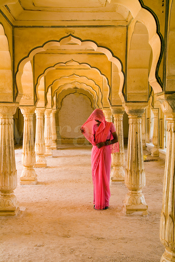 Graphic arches with colorful Hindu woman in sari, Amber, Fort temple, Rajasthan, Jaipur, India