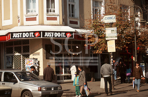 "Sofia, Bulgaria. People on the street; ""Just do it"" sign on a NIKE shop."