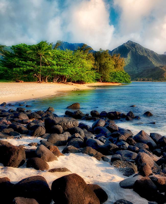 Hanalei Bay with white sand and black volcanic rocks. Kauai, Hawaii.