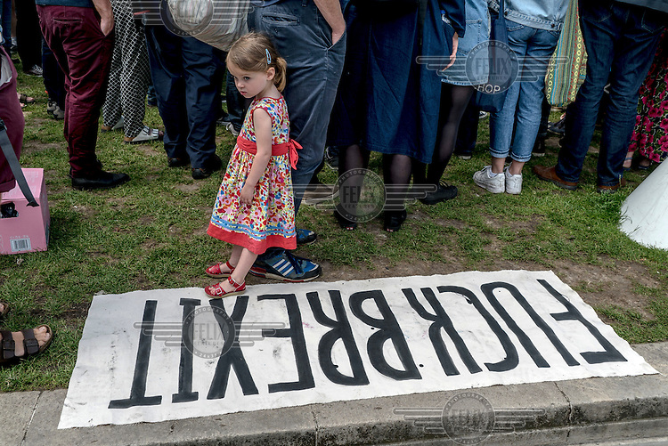A young girl stands on a banner that reads: 'FUCK BREXIT' at a demonstration in Parliament Square protesting the victory of the 'leave' (the EU) side in the EU reeferendum.