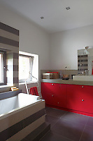 The upstairs bathroom of this 1950s pavilion has been created in waxed concrete, decorated with a bold stripe framing the window and bath surround and  complemented with scarlet red storage