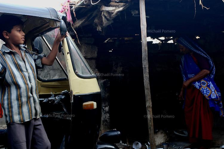 08.10.2008 Dwarka(Gujarat)<br /> <br /> A young boy looking in the rear-view mirror of a rickshaw and a women cooking outside of their family house.<br /> <br /> Un jeune garcon se regardant dans le retroviseur d' un rickshaw et une femme en train de cuisiner a l exterieur de la maison familiale.