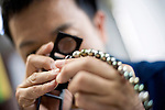 Kazuhito Komatsu, president of Komatsu Cutting Factory, looks through a loupe at faceted pearls he cuts and processes at his company in Kofu City, Yamanashi Prefecture, Japan on 16 Oct. 2012.  Komatsu's father developed a world-first technique for cutting the peals. Photographer: Robert Gilhooly