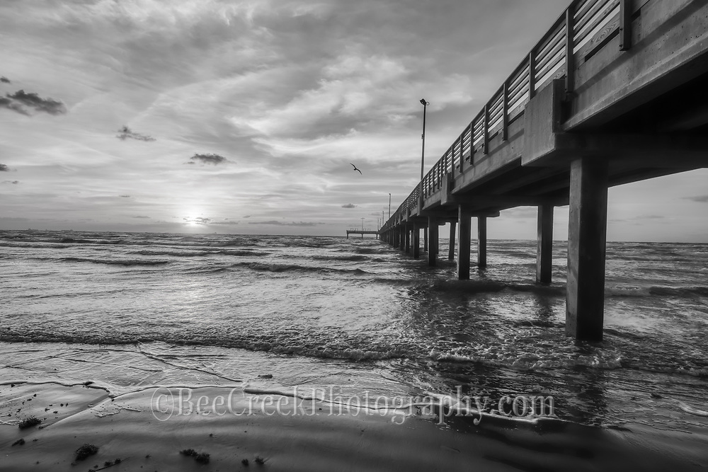 This is a fishing pier along the Texas coast taken as the sun was coming up in an almost black and white version. This coastal seascape with all the element of sand, surf, beach, clouds, sunrise, wooden pier, fishing, gulf, ocean, wave and all other element of the coast done in black and white.