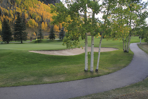 Paved pathway surrounding a sand trap and golf fairway, Vail, Colorado.