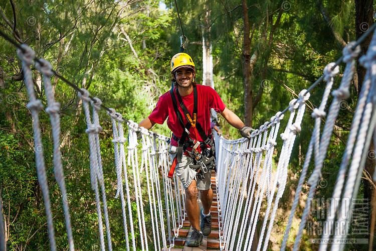 Happy male tourist crosses suspension bridge while Ziplining on the Big island with Kohala zipline