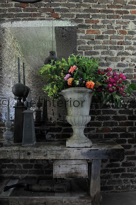 An antique stone urn containing an informal flower arrangement sits on top of a rustic workbench in the hallway