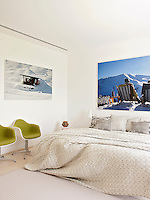 A modern bedroom decorated in neutral tones. Two photographs by Philipp Hofmann and two Eero Saarinen chairs upholstered in lime green bring a spot of colour to the room.