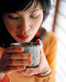JAPAN, Kyushu, close-up of a young woman a holding teacup